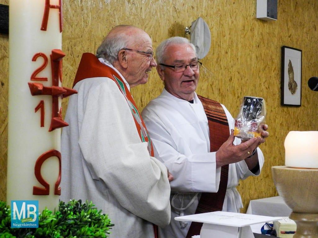 Pfarrer Alfred Brömmelhaus bekommt von Diakon Friedel Nähring zum Dank einen Tee samt Tasse.