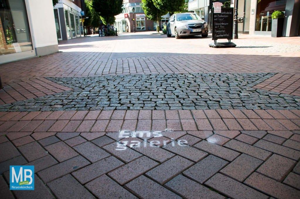 In der Neuenkirchener Fußgängerzone wird mit Graffitis für dei Emsgalerie geworben. | Foto: Klausing